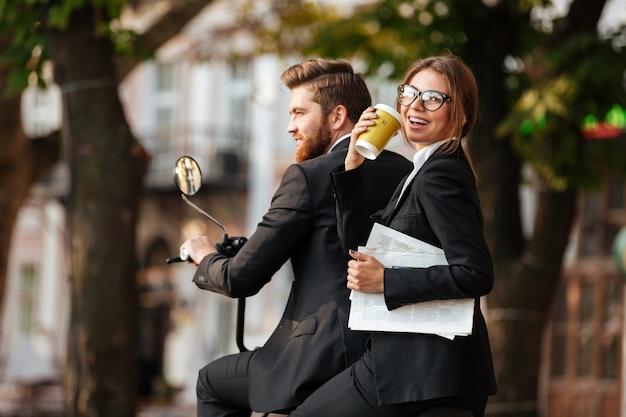 Vista traseira do alegre casal elegante monta na moto moderna