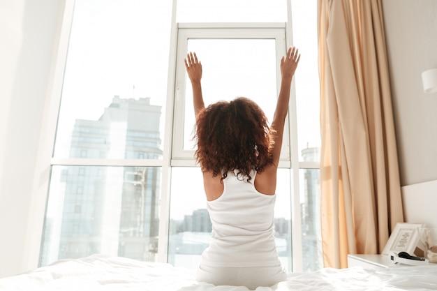 Vista traseira do alongamento mulher em casa pela manhã