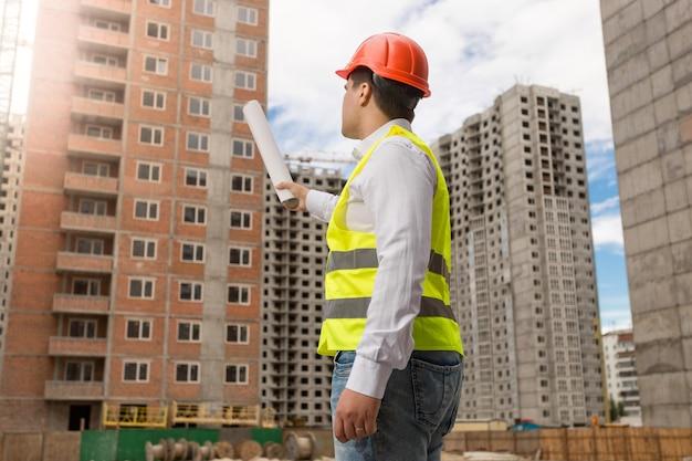 Vista traseira do arquiteto no capacete de segurança apontando com plantas laminadas para o prédio em construção