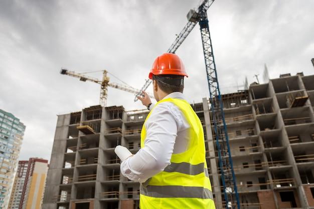 Vista traseira do arquiteto no capacete de segurança apontando para um prédio em construção