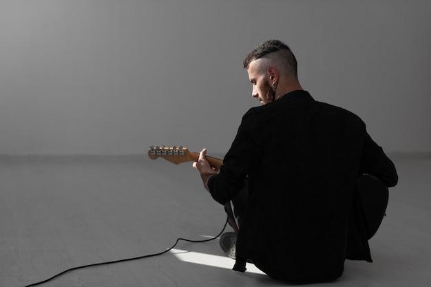 Vista traseira do artista masculino tocando guitarra elétrica