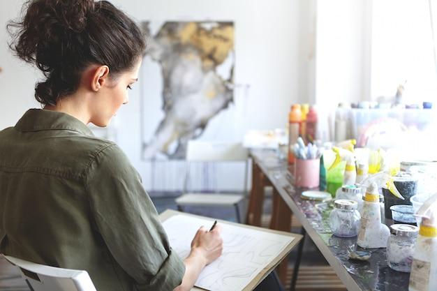 Vista traseira do artista morena jovem mulher caucasiana em camisa cáqui, segurando o lápis, desenhando na oficina com tintas na mesa perto dela. conceito de arte, criatividade, pintura, hobby, emprego e ocupação