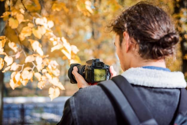 Vista traseira do atirador de vídeo do blogger vlogger filmando o parque colorido do outono em sua câmera. conceito de tiroteio de fotos ou vídeos de outono