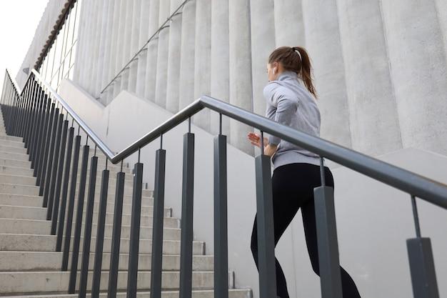 Vista traseira do atleta corredor correndo nas escadas. aptidão da mulher é correr ao ar livre.