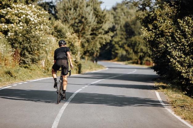 Vista traseira do atleta masculino em roupas esportivas e capacete protetor de bicicleta durante os dias ensolarados.