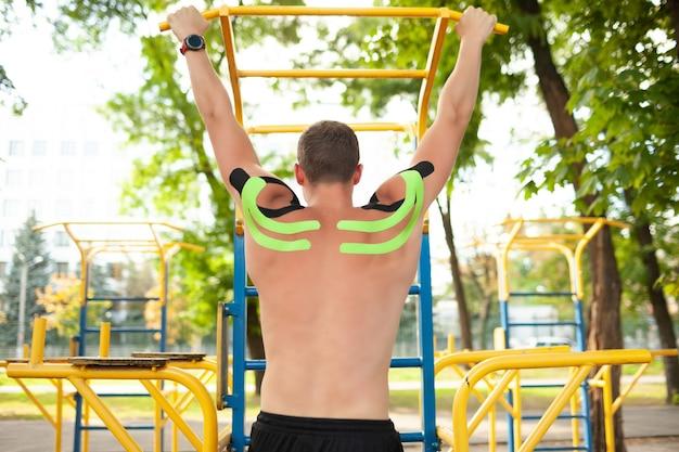 Vista traseira do atleta profissional masculino com fita cinesiológica colorida nas costas