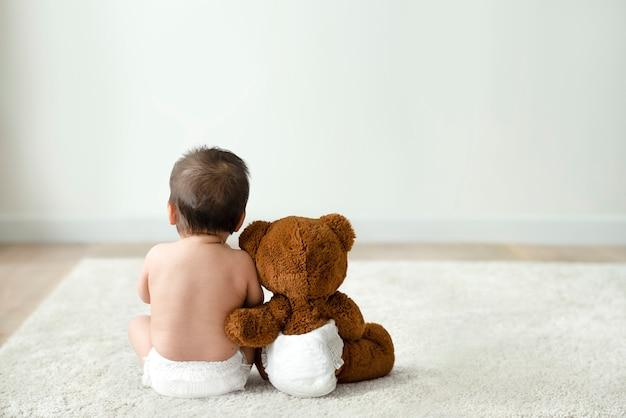 Vista traseira do bebê e do ursinho de pelúcia com espaço de design