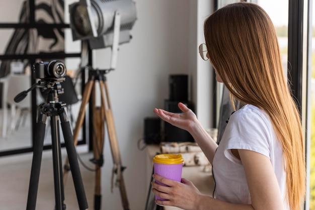 Vista traseira do blogger gravação com câmera profissional, segurando uma caneca de viagem