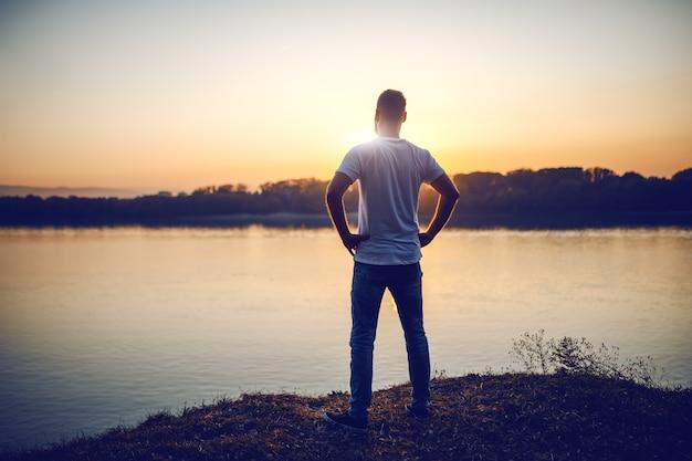 Vista traseira do bonito homem caucasiano de pé com as mãos nos quadris na falésia e olhando para o rio e o belo pôr do sol.