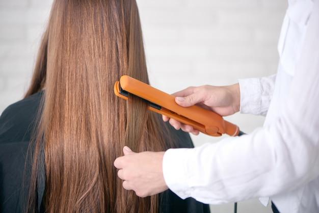 Vista traseira do cabeleireiro, alisando os cabelos castanhos compridos do cliente.