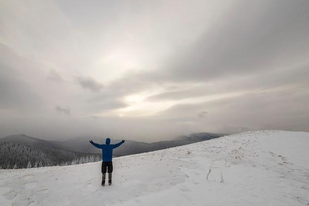 Vista traseira do caminhante do turista em roupas quentes com mochila em pé com os braços erguidos na clareira coberta de neve na montanha da floresta de abetos e céu nublado copie o fundo do espaço.