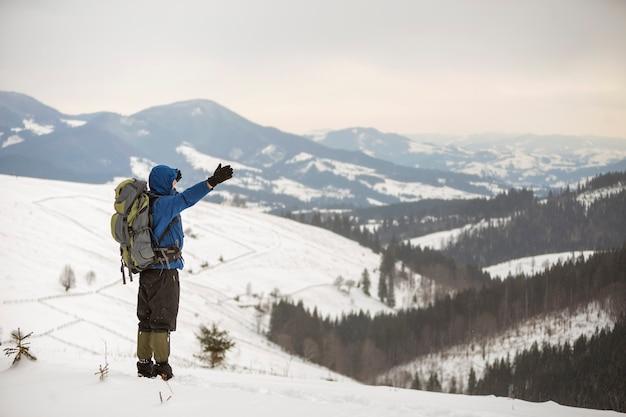 Vista traseira do caminhante do turista em roupas quentes com mochila em pé com os braços erguidos na clareira na clareira na cópia de fundo de espaço do cume da montanha lenhosa e céu nublado.