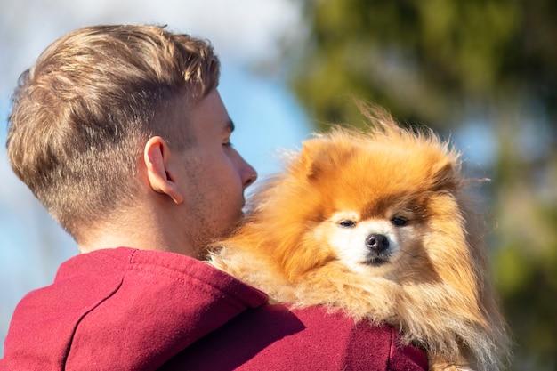 Vista traseira do cara, jovem com cachorro pomeranian spitz, cachorrinho doce bonito nas mãos. as pessoas adoram animal de estimação, conceito de animal. garoto espera, abraça seu lindo cachorro.