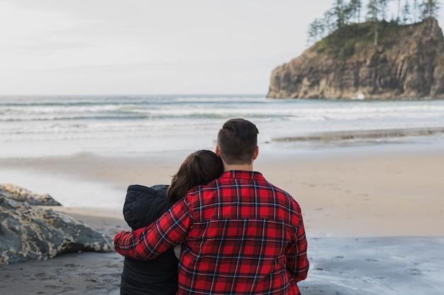 Vista traseira do casal abraçado na praia Foto gratuita
