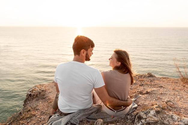 Vista traseira do casal apreciando o pôr do sol