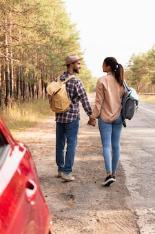Vista traseira do casal caminhando com as mochilas nas costas