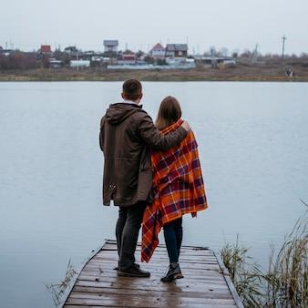 Vista traseira do casal com cobertor ao ar livre admirando a vista do lago