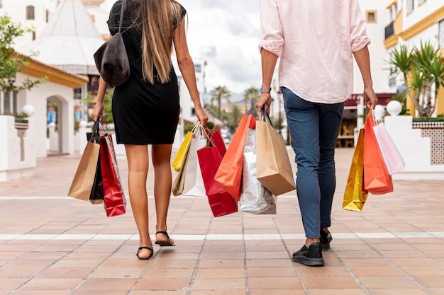 Vista traseira do casal com sacos de compras