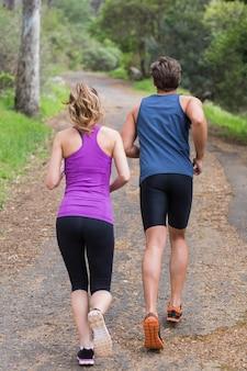 Vista traseira do casal correndo na estrada