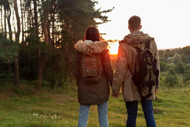 Vista traseira do casal curtindo o nascer do sol na natureza