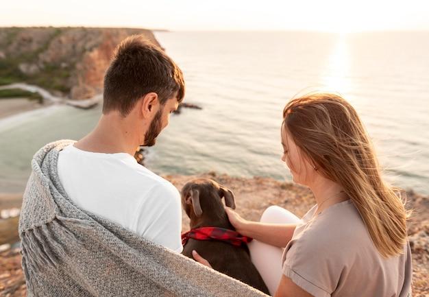 Vista traseira do casal curtindo o pôr do sol com o cachorro