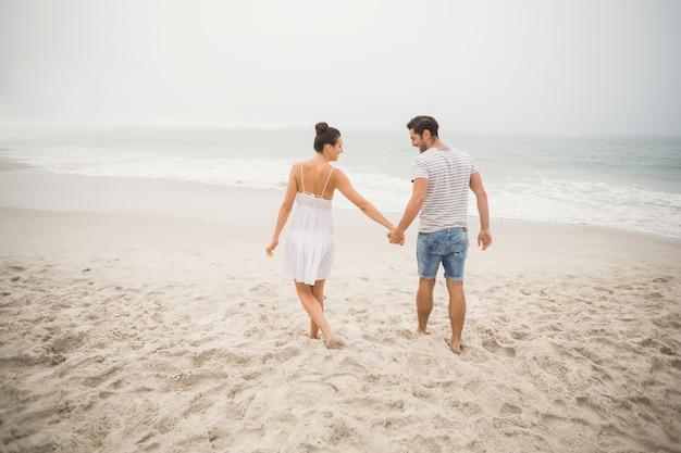 Vista traseira do casal de mãos dadas e caminhando na praia