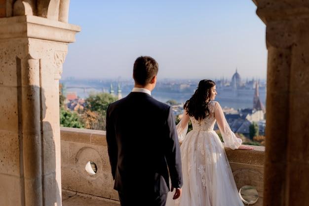 Vista traseira do casal de noivos no dia ensolarado no topo de um edifício arquitetônico de pedra com um cenário bonito da cidade