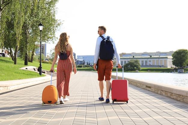 Vista traseira do casal de turistas de mãos dadas e arrastando a bagagem, passeando visitando a rua, ao ar livre.