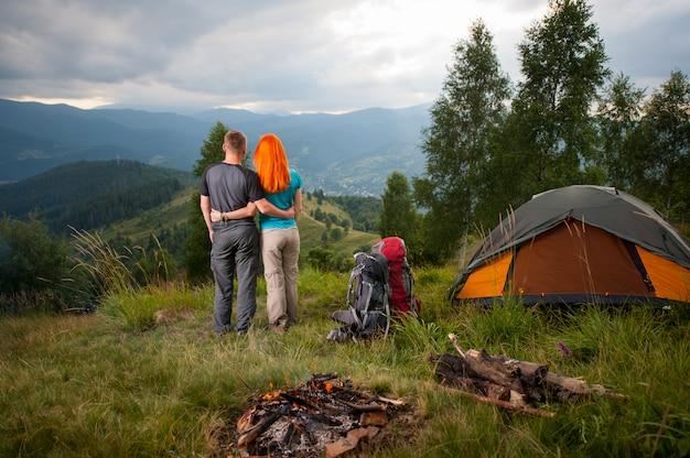 Vista traseira do casal de turistas em pé perto da fogueira, mochilas e tenda