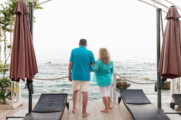 Vista traseira do casal de turistas mais velhos na praia