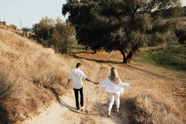 Vista traseira do casal feliz em roupas brancas, caminhando e de mãos dadas no parque.