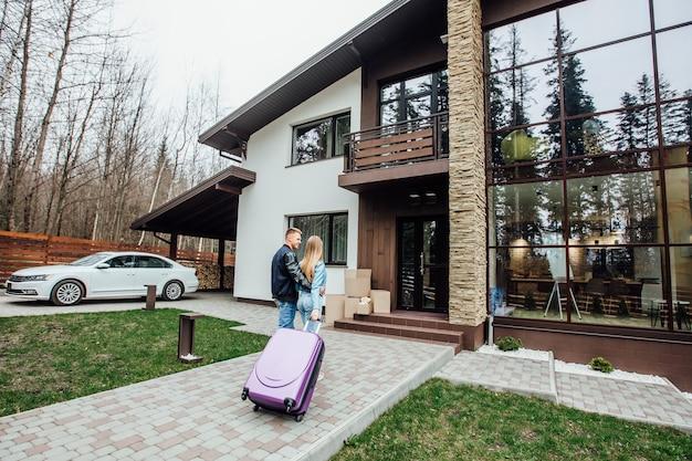 Vista traseira do casal feliz está de pé perto de sua casa moderna e abraçando, segurando a mala.