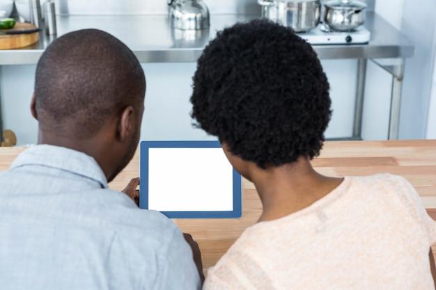 Vista traseira do casal grávida olhando tablet digital na cozinha