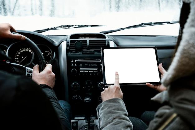 Vista traseira do casal no carro, consultando o tablet durante uma viagem