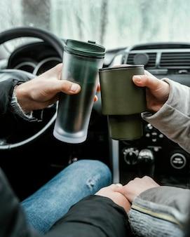 Vista traseira do casal no carro durante uma viagem brindando com bebidas quentes