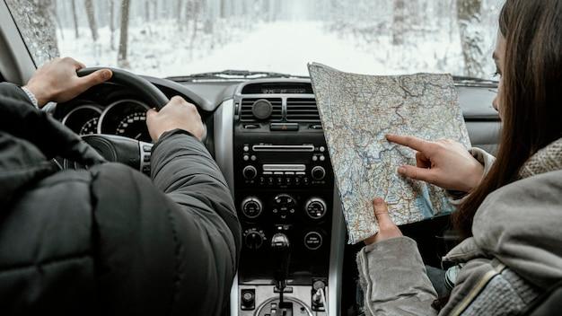 Vista traseira do casal no carro durante uma viagem, consultando o mapa