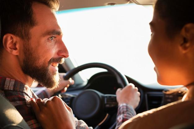 Vista traseira do casal olhando um para o outro no carro