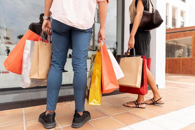 Vista traseira do casal segurando sacolas de compras