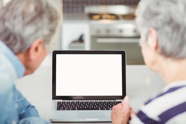 Vista traseira do casal sênior usando laptop