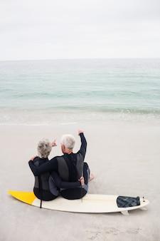 Vista traseira do casal sentado na prancha de surf