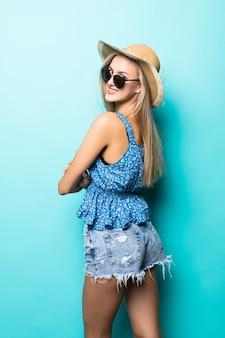 Vista traseira do chapéu de palha de verão de mulher sorriso animado sobre fundo azul.