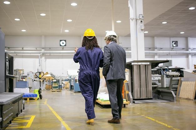Vista traseira do chefe em pé na fábrica e ouvindo o trabalhador da fábrica