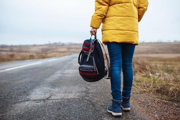 Vista traseira do close up de uma mulher caminhando pela estrada solitária com uma mochila na mão.