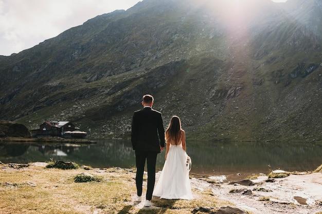 Vista traseira do comprimento total de uma noiva e do noivo irreconhecível, caminhando para as montanhas contra o nascer do sol.
