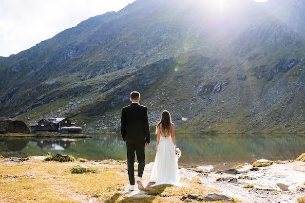 Vista traseira do comprimento total do noivo irreconhecível e noiva sentada à beira de um lago nas montanhas contra o nascer do sol.
