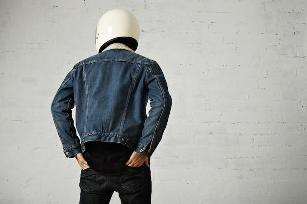 Vista traseira do corpo de jovem motociclista usando capacete, camisa preta de manga comprida henley e jaqueta jeans com as mãos nos bolsos traseiros das calças