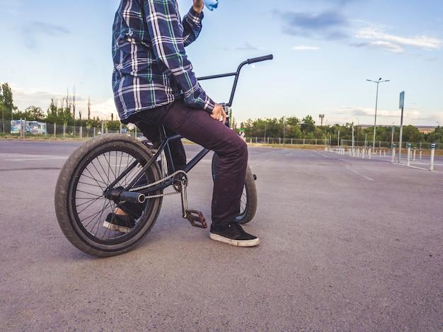 Vista traseira do corpo do adolescente sentado relaxando na bicicleta bmx