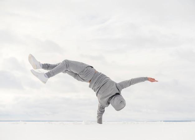Vista traseira do dançarino equilibrando seu corpo com uma mão
