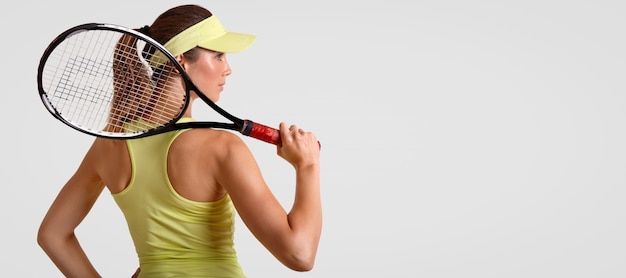 Vista traseira do desportivo feminino gosta de tênis, detém raquete, veste camiseta casual e boné, pronto para jogar e competir, fica contra branco