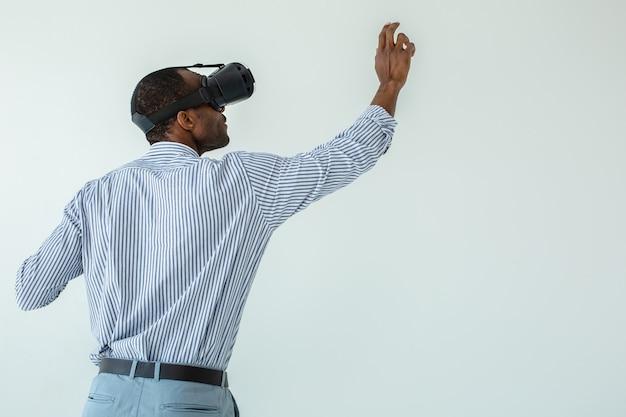 Vista traseira do empresário afro-americano usando óculos de realidade virtual enquanto escreve no quadro.